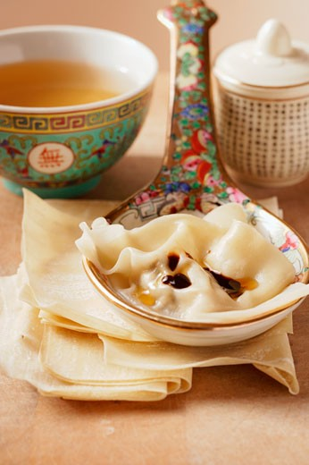 Won tons on spoon; clear broth in small bowl : Stock Photo