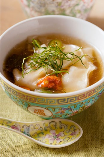 Stock Photo: 1532R-8603 Broth with won tons, chili sauce & strips of lemon leaves