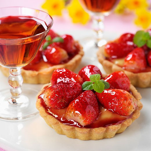 Strawberry tartlets with mint; dessert wine : Stock Photo