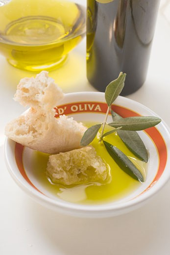 Olive oil in bowl with white bread and olive branch : Stock Photo