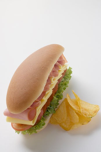 Ham, cheese, tomato and lettuce sandwich with crisps : Stock Photo
