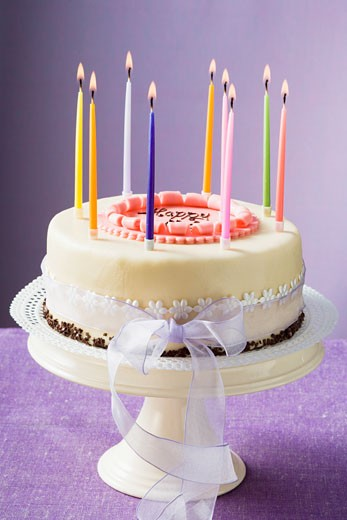Birthday cake with burning candles : Stock Photo
