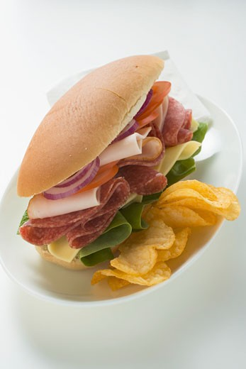 Salami, ham, cheese and salad sandwich with crisps : Stock Photo