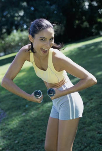 Portrait of a teenage girl exercising with dumbbells : Stock Photo