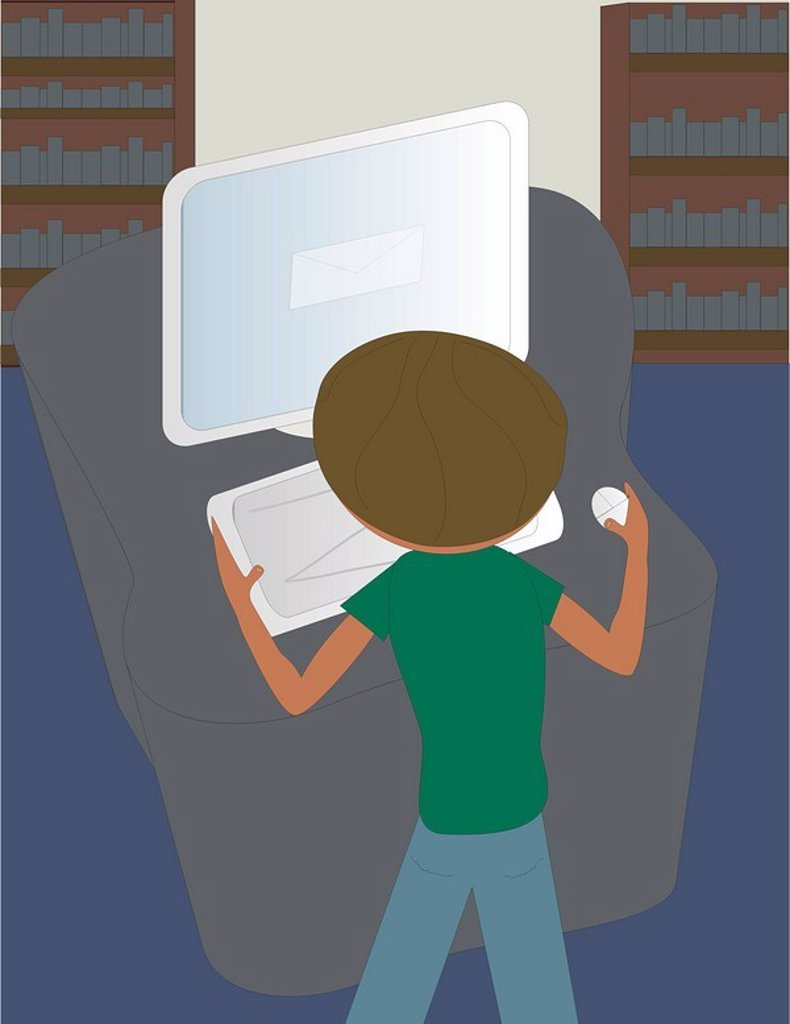 A boy using a computer at the library : Stock Photo