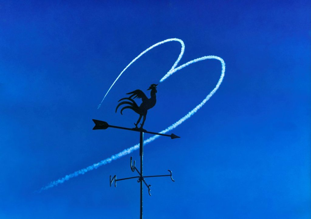 Weather vane against heart shaped vapour trail : Stock Photo