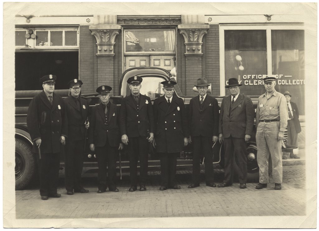 Stock Photo: 1539-110 Portrait of police officers standing in front of a car, 1928