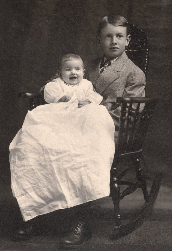 Boy sitting with his sister in a rocking chair, c. 1915 : Stock Photo