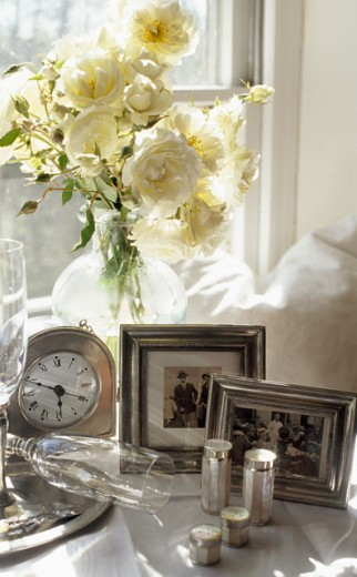 Stock Photo: 1545-148 Close-up of picture frames with a flower vase and a clock near a window