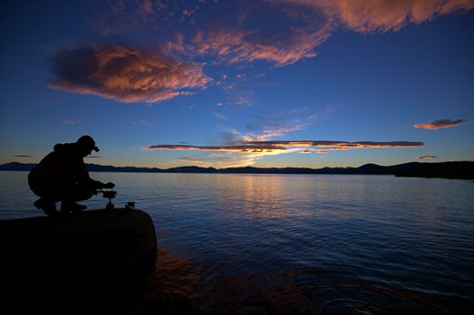Silhouette of a hiker preparing food at the lakeside, Lake Tahoe, Nevada, USA : Stock Photo
