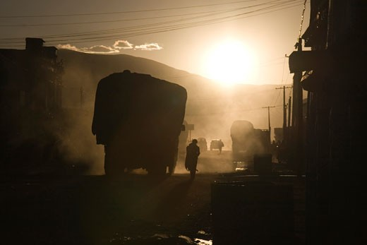 Stock Photo: 1546-629 Silhouette of a person standing near a truck on the street, Tingri, Tibet, China