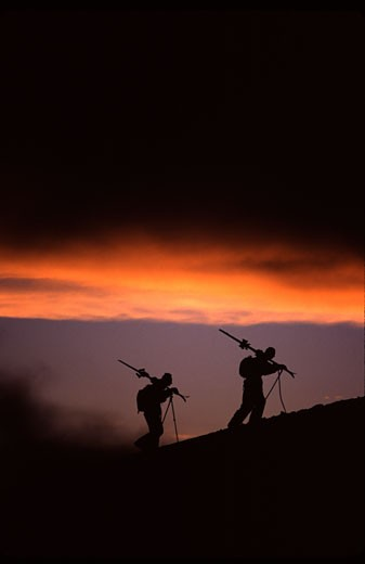 Silhouette of two skiers hiking at sunset after a storm while skiing, Mt Hood, Mt Hood National Park, Oregon, USA : Stock Photo