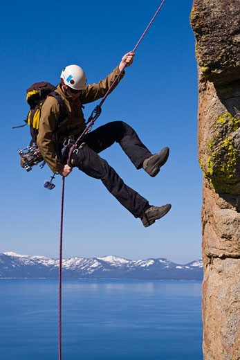 Man rappelling off a cliff, Lake Tahoe, Nevada, USA : Stock Photo