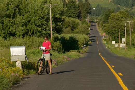 Woman reading a mail by a country mailbox while riding a bicycle, Parkdale, Hood River County, Oregon, USA : Stock Photo