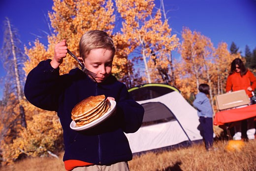 Stock Photo: 1546-931 Boy holding a plate of breads and a fork while camping, Truckee, Nevada County, California, USA