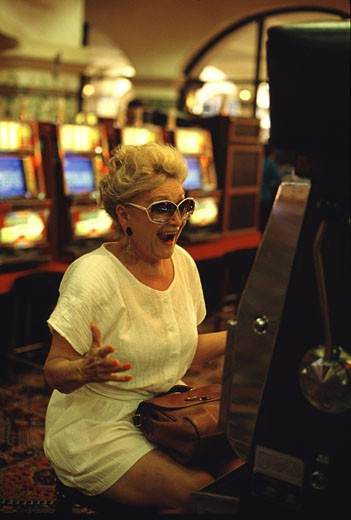 Stock Photo: 155-1175 Mature woman gambling on a slot machine in a casino, Laughlin, Nevada, USA
