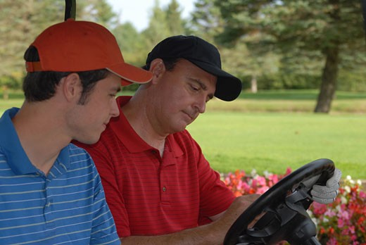 Stock Photo: 155-1566 Mature man and his son updating scorecard in a golf cart
