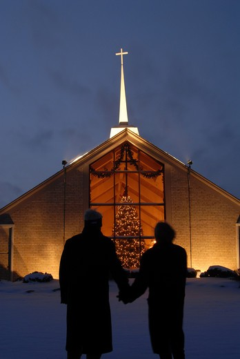 Silhouette of a couple standing in front of a church during Christmas