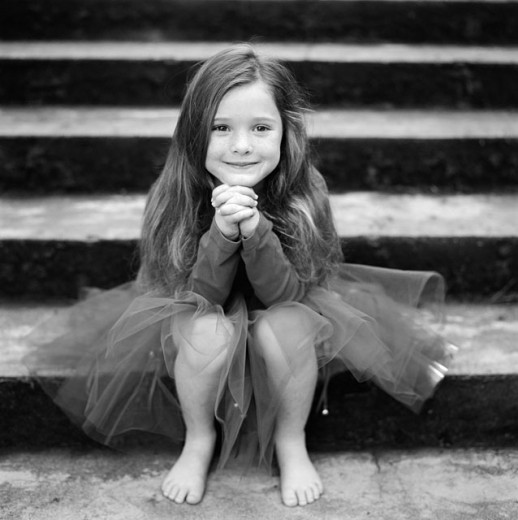 Portrait of a girl sitting on steps and smiling : Stock Photo