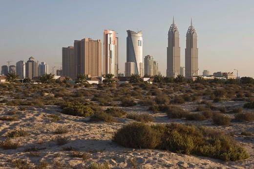 Modern office buildings contrasting with desert landscape, Dubai Marina area : Stock Photo