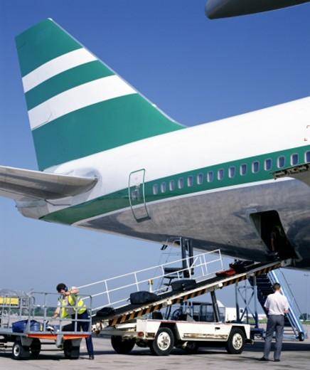 Loading luggage onto airplane : Stock Photo