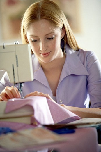 Teenage girl using sewing machine : Stock Photo