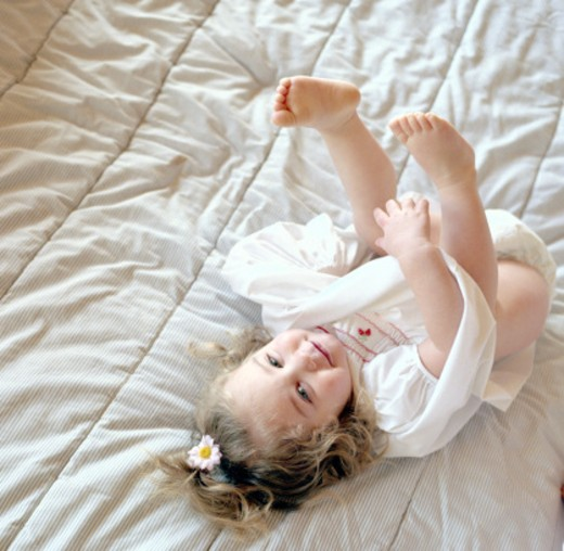 Toddler lying on bed : Stock Photo