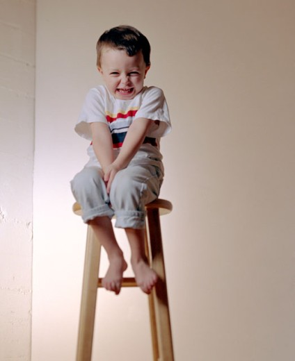 Boy sitting on a stool : Stock Photo