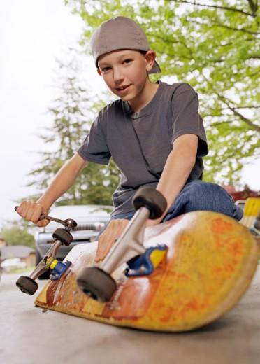 Boy fixing skateboard : Stock Photo