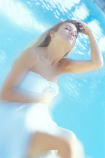 Woman relaxing by swimming pool : Stock Photo