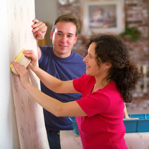 Couple putting up wallpaper : Stock Photo