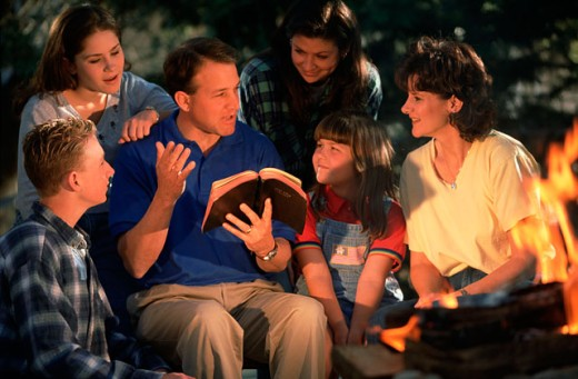 Family reading the bible around a campfire : Stock Photo