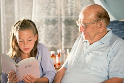 Girl reading the bible to her grandfather : Stock Photo