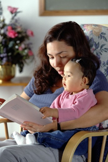 Mother reading to baby from the bible : Stock Photo
