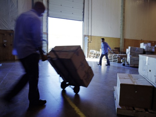 Worker moving boxes : Stock Photo