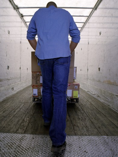 Stock Photo: 1555R-237068 Worker pushing boxes