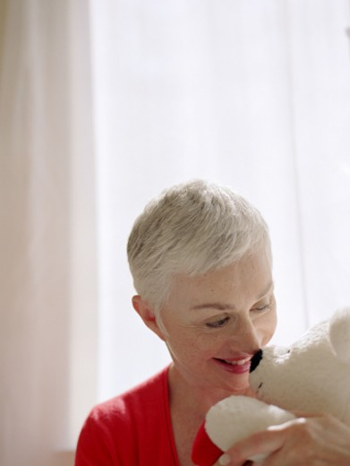 Nostalgic senior woman with teddybear : Stock Photo