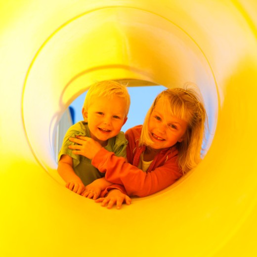 Happy children in playground slide : Stock Photo