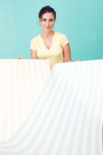 Woman showing wallpaper choices : Stock Photo