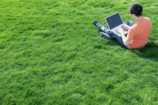 Boy sitting in grass using laptop : Stock Photo