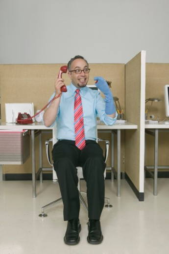 Businessman on telephone playing with sock puppet : Stock Photo