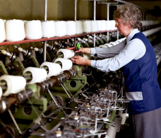 Woman working in textile plant : Stock Photo