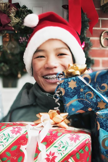 Stock Photo: 1555R-308234 Smiling boy holding Christmas gifts