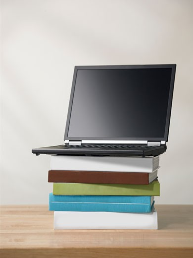 Laptop computer on pile of books : Stock Photo