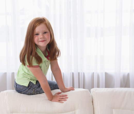 Stock Photo: 1555R-309149 Portrait of girl sitting on couch