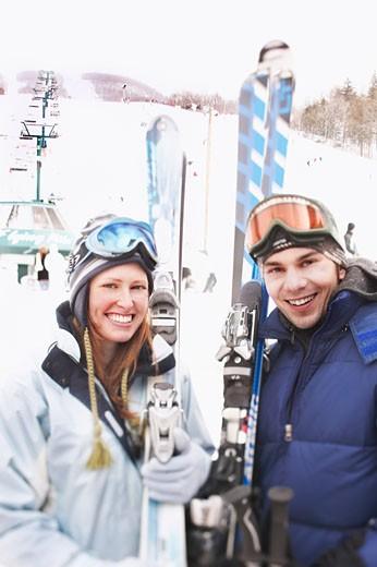 Couple holding skis : Stock Photo