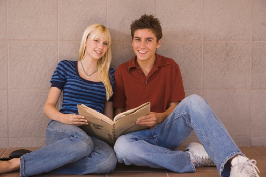 Teenage couple holding book together : Stock Photo