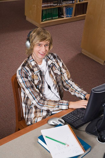 Stock Photo: 1555R-309893 Teenage boy working on computer in library