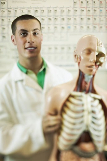 Teenage boy standing next to model of human body : Stock Photo