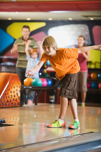 Boy bowling with his family : Stock Photo